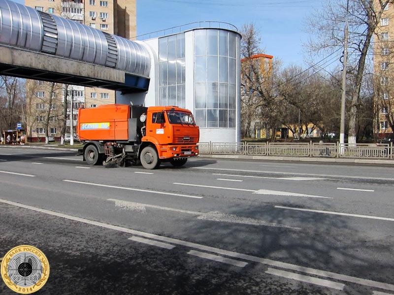 Мусороуборочная машина чистит проезжую часть на       Ильинском шоссе в подмосковном городе Красногорске.