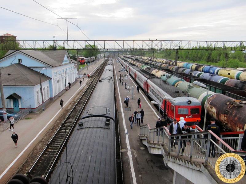Электричка из Москвы прибывает в Волоколамск       совсем не на первый путь, как этого хотелось бы многим. Она вклинивается между пассажирским поездом и несколькими       товарняками с цистернами, каждый из которых похож на связку сосисок.
